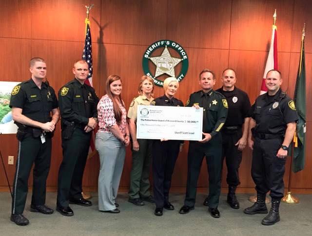Sheriff Scott Israel presents a check to the BPMA Board.